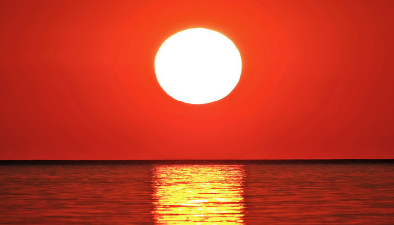 The sun sets over water, appearing totally white against a deep red sky with an orange reflection over water