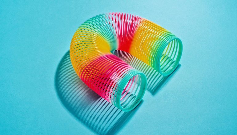 A rainbow-colored slinky is bent into a rainbow shape on a blue background