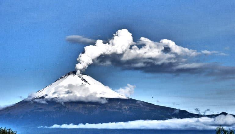 A snow-covered volcano spews smoke against a bright blue sky