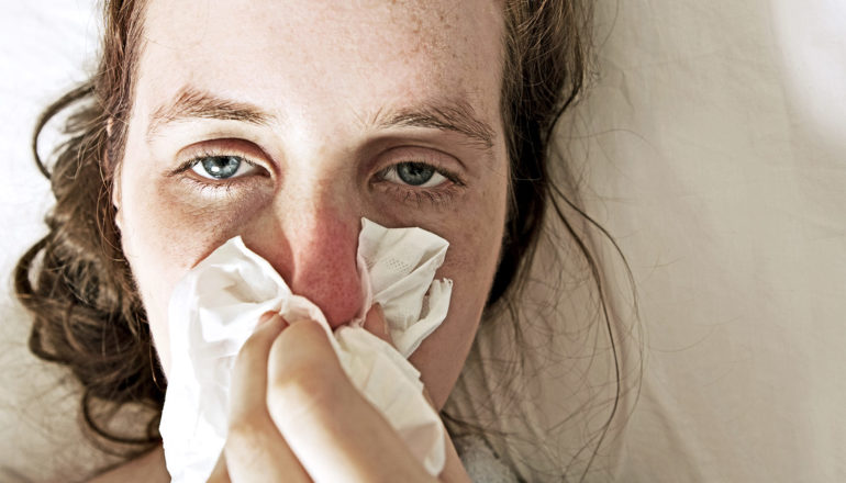 A woman with a cold blows her red nose while looking miserable on a white sheet