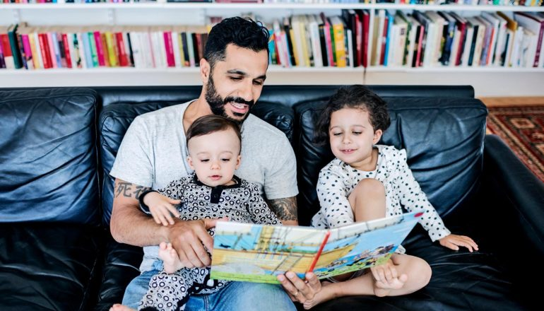A dad in a gray t-shirt and blue jeans reads to his two young children on a black couch with a bookshelf in the background