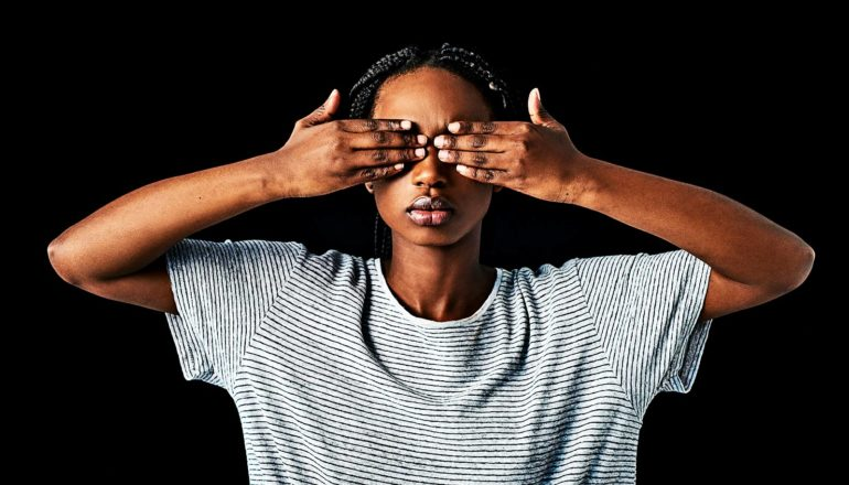 A woman in a white and black striped t-shirt covers her eyes with her hands against a black background