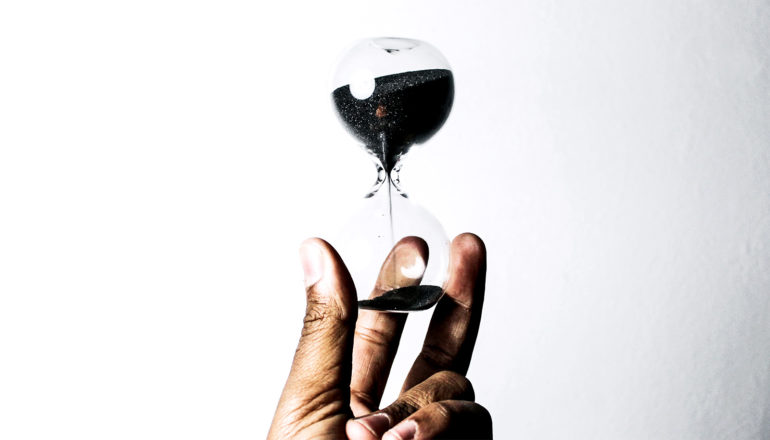A person holds an hourglass with dark sand inside against a white background
