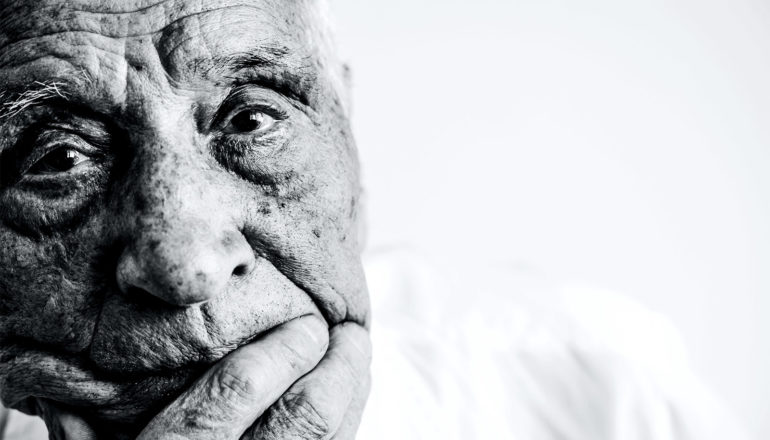 An older man looks sad as he puts his hand to his chin
