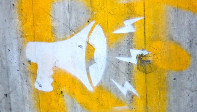 A megaphone is painted on a concrete wall in white, with some yellow paint on the wall behind it