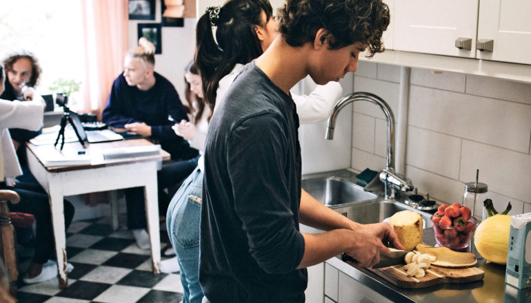 teen cuts fruit in kitchen among other people