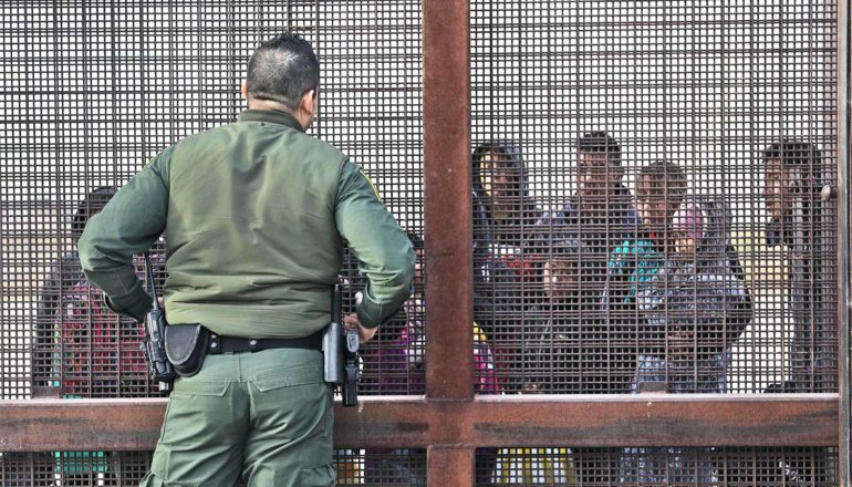 A border patrol guard stands on one side of a fence with families on the other