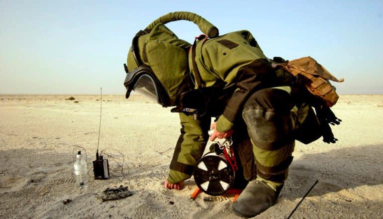 person in bomb suit and hood kneels in desert