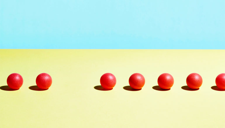 A row of red balls sits on a yellow surface with a blue background, with one ball missing from the series