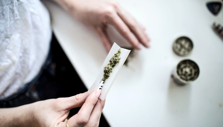 A woman puts marijuana into a rolling paper to roll a joint