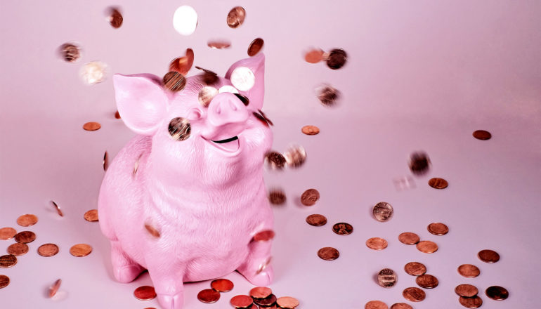 A piggy bank sits on a pink background with coins raining down on it. It's smiling face is looking up as the coins fall down