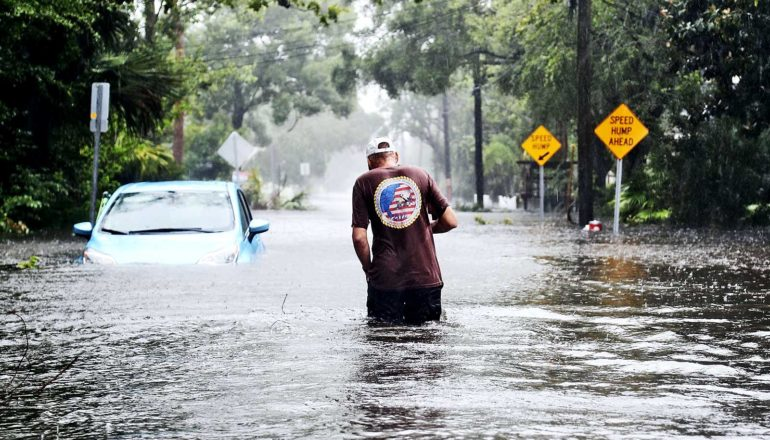 A man in dark pants, a brown t-shirt, and a white hat walks through flooded streets with water up to his waist. A blue, half-submerged car stands to his left