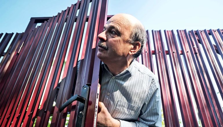 A man opens a fence door and looks out to his right