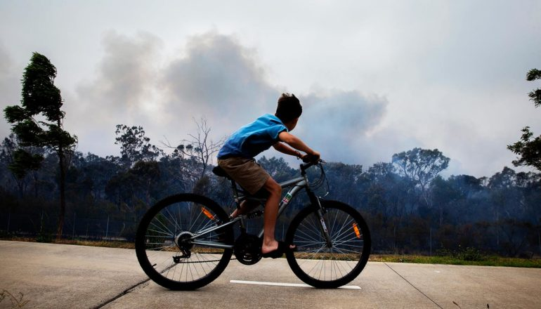 child rides bike with smoke from wildfire behind in the distance