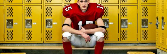 A young football player sits in a locker room in uniform with his helmet off