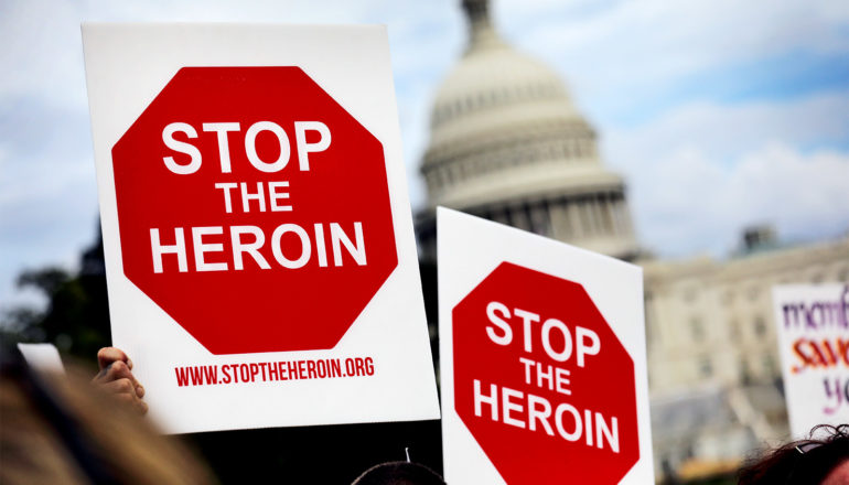 """Two people hold up signs that read """"Stop the Heroin"""" with the US Capitol building in the background"""