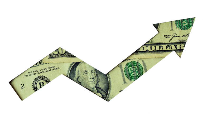 $100 bill behind arrow-shaped cut-out in white paper