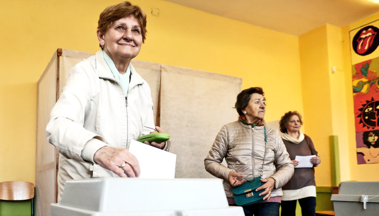 A woman smiles as she places her ballot in a box, with the voting booth and two other voters behind her in a yellow room