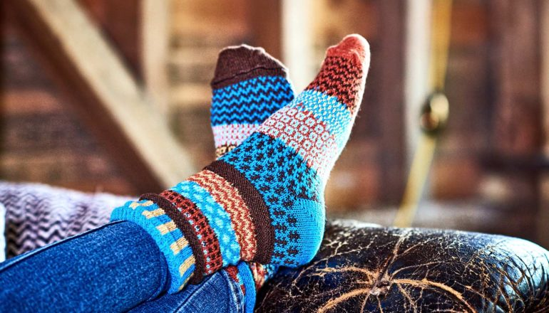 A person wearing colorful socks puts their feet up on the arm of a couch