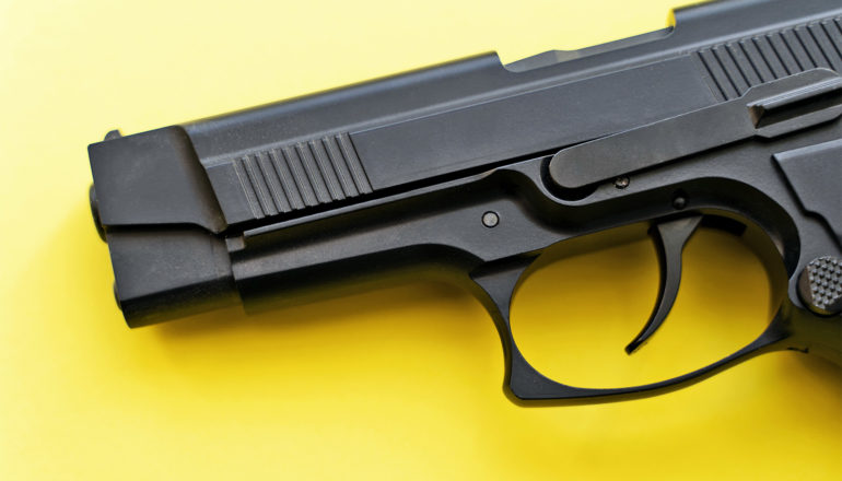 A black handgun sits on a yellow background