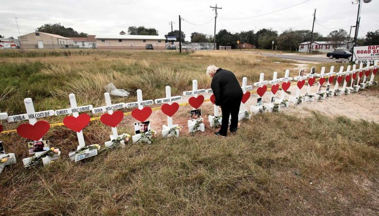 person stands before long line of crosses with hearts and photos attached to each