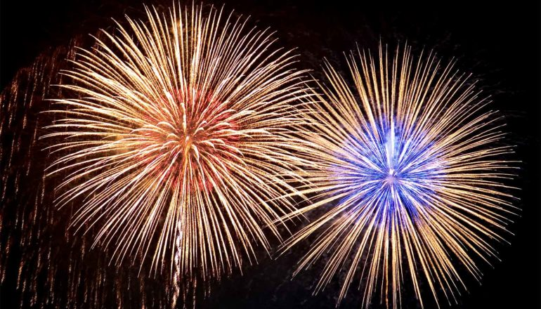 Two fireworks explode next to each other, one red at the center and the other blue, against a black night sky