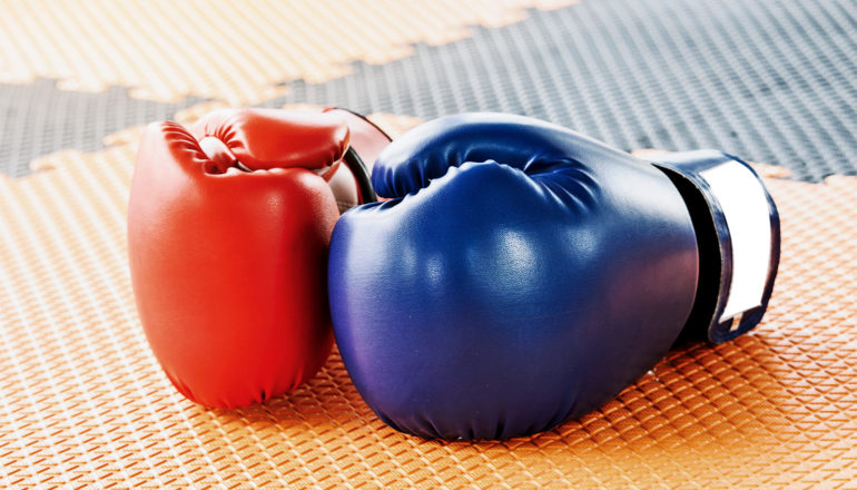 Two boxing gloves sit on a gym floor, one blue and one red
