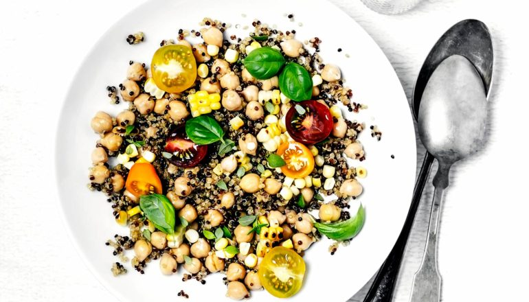quinoa, chickpeas, tomatoes, and basil on plate with spoons