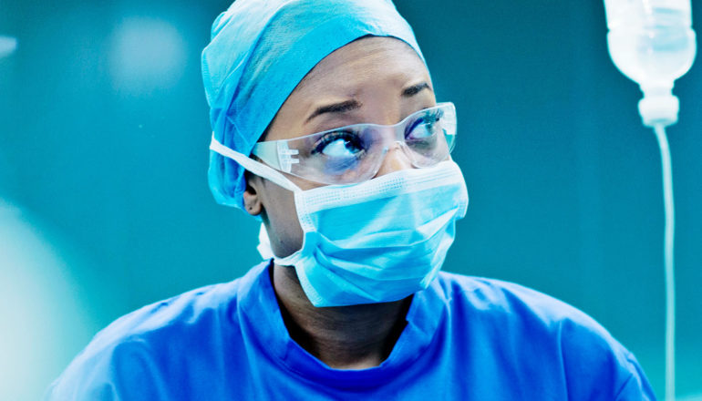 A doctor with face mask and goggles on looks to her left while in the operating room