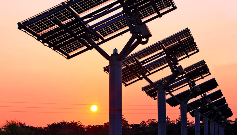 The sun sets in the distance, while a row of solar panels sit in the foreground