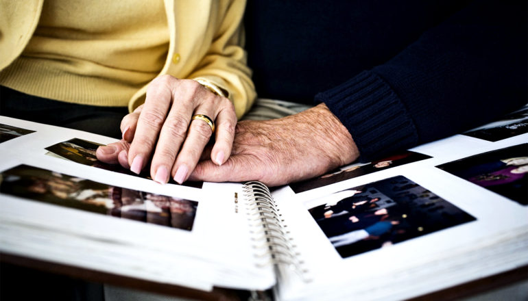 An older couple look at a photo album, with a woman in a yellow sweater putting her hand on his