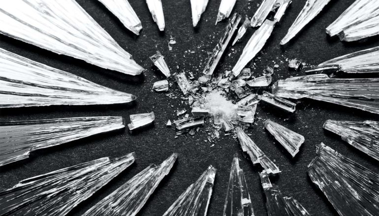 Shattered glass sits on a black background, with some light shining onto the pieces