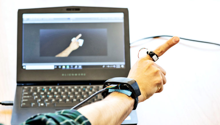 A researcher wearing the AuraRing system shows off the hand and finger tracking, with his hand showing up on a computer screen