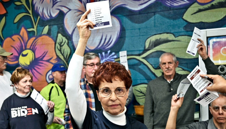 A woman with glasses and red hair holds up a piece of paper, with people behind her against a colorful painted wall