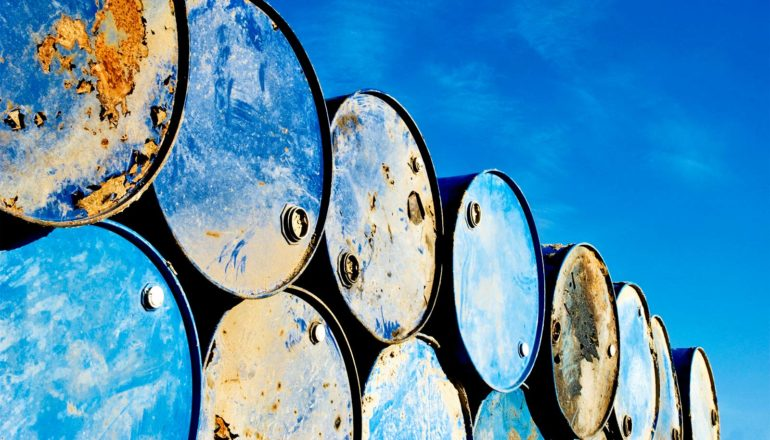 Rows of blue, rusting barrels sit against a blue sky