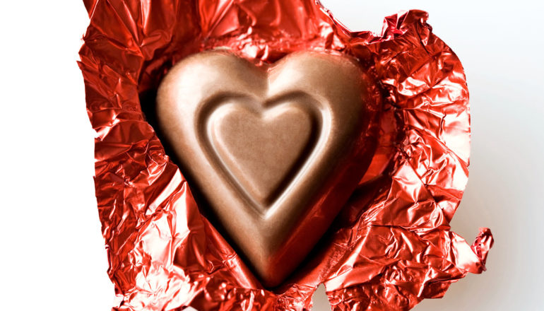 A heart-shaped piece of chocolate sits on its unwrapped red, shiny wrapper