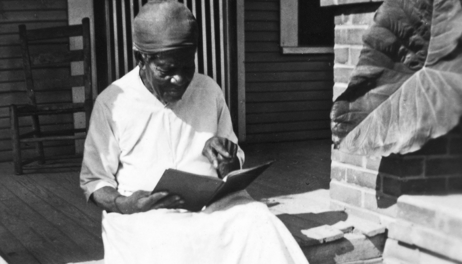Mary Armstrong sits on a porch reading, while wearing a white dress and head wrap