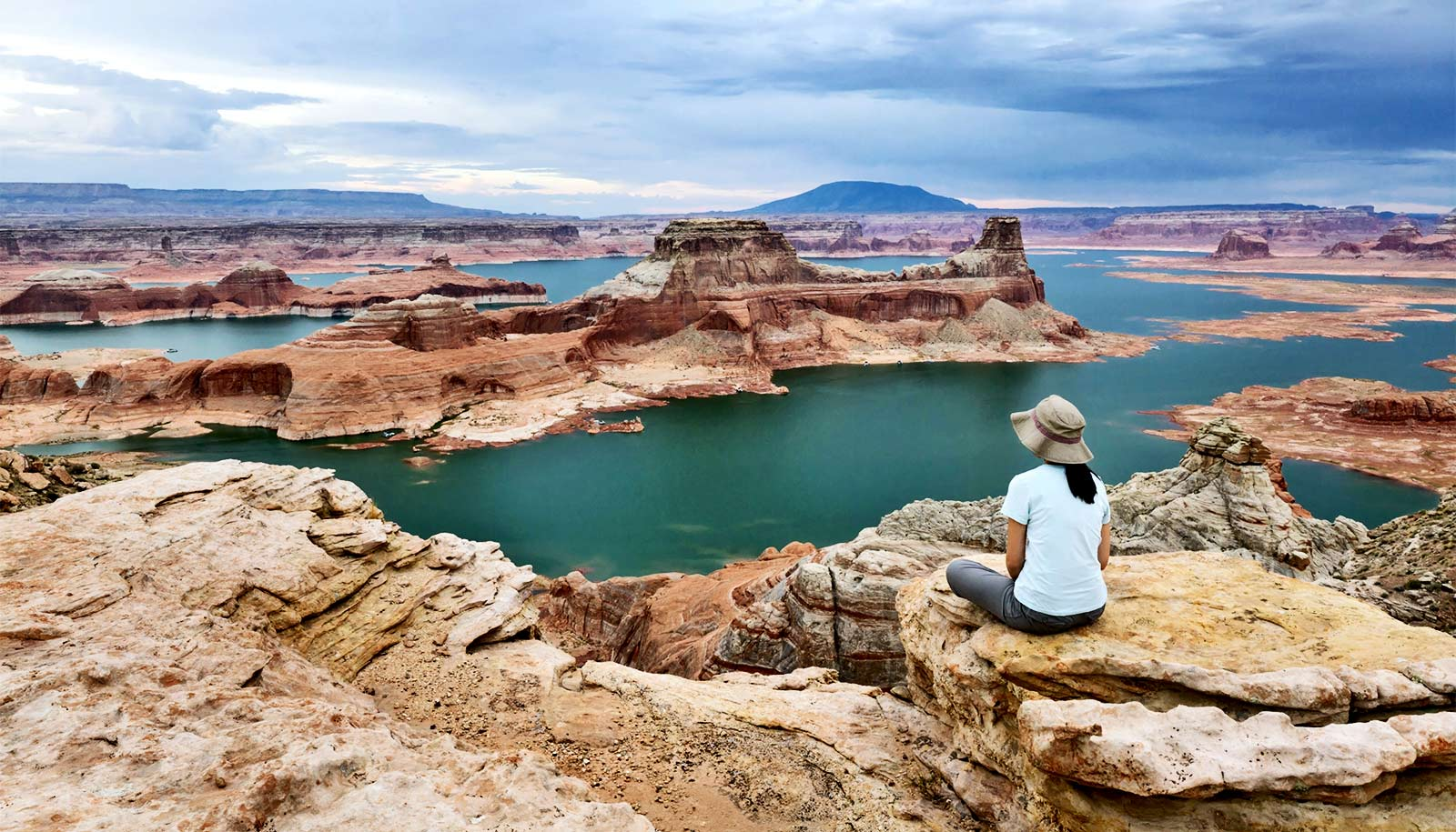 A woman looks out over Lake Powell, with patches of water broken up by red rock formations