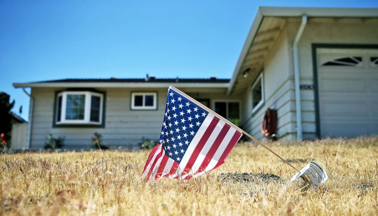 low-angle view of small US flag on dead lawn in front of house