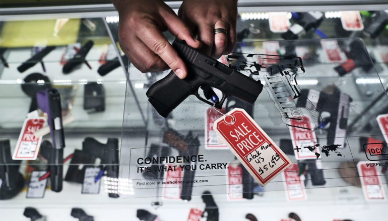A gun shop owner holds a black pistol with a red sale tag on it over a glass case containing many pistols