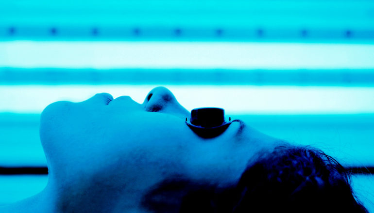 A woman lies in an indoor tanning bed, with her bathed in blue light, while wearing black goggles over her eyes