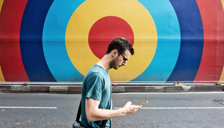 A man walks down the street looking down at his phone. The wall behind him is a multi-colored target design that's centered behind his head