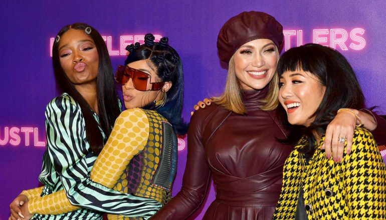 """Keke Palmer, Cardi B embrace, make kissy faces next to J Lo with arm around Constant Wu. Step & repeat behind them says """"Hustlers"""""""