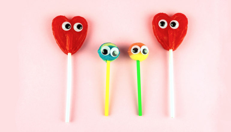 two larger heart-shaped lollipops with googly eyes with two smaller, round lollipops with googly eyes between them