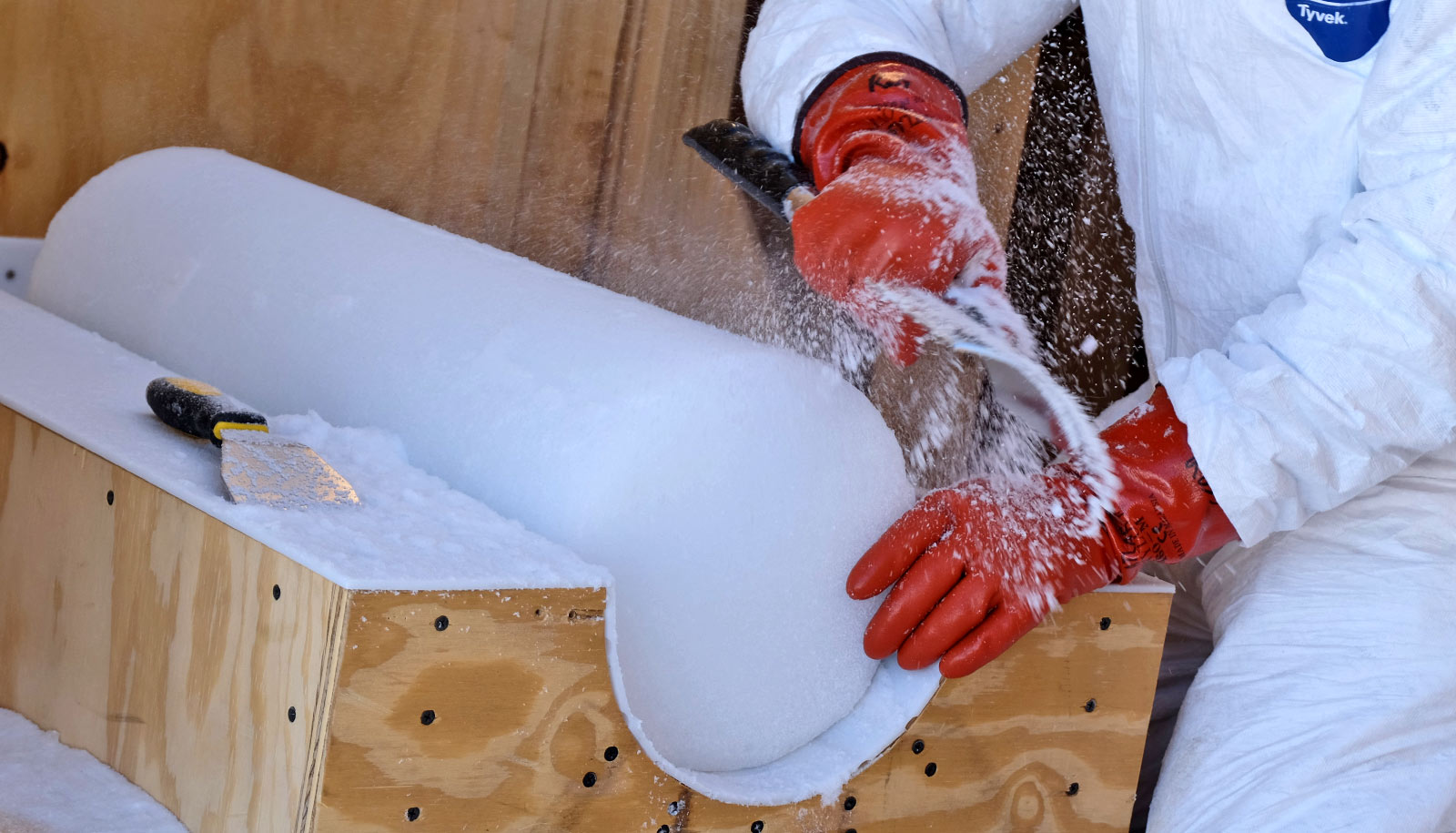 gloved hands use tool to scrape ice core in wooden holder