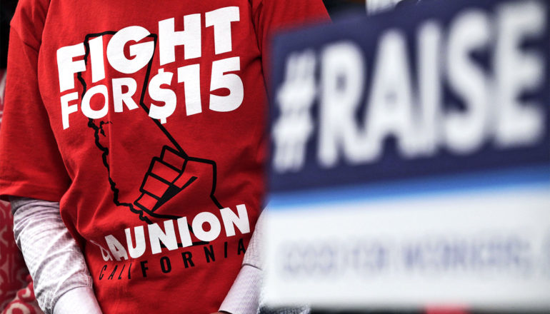 """A person wears a red t-shirt that says """"Fight for $15"""" with a picture of a raised fist over the state of California. Another person holds a sign that reads, """"#RAISE."""""""