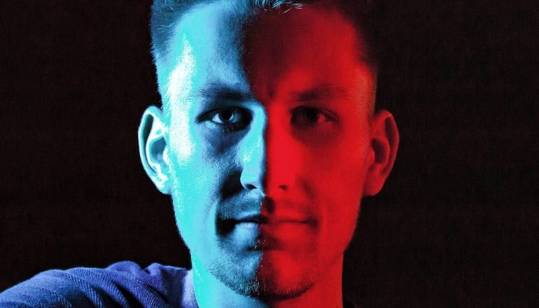 A young man looks at the camera with half his face blue and half red, with a black background