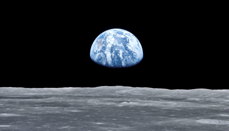 Earth rises over the surface of the moon, blue against the black background of space