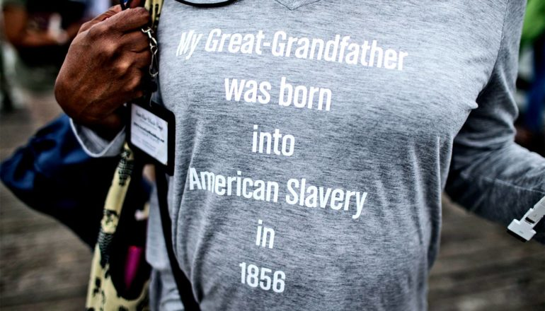 """A woman wears a t-shirt that reads, """"My Great-Grandfather was born into American Slavery in 1856"""""""