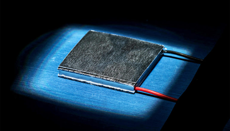 A small piece of black metal sits on a blue surface with a black and a red wire coming out of the bottom